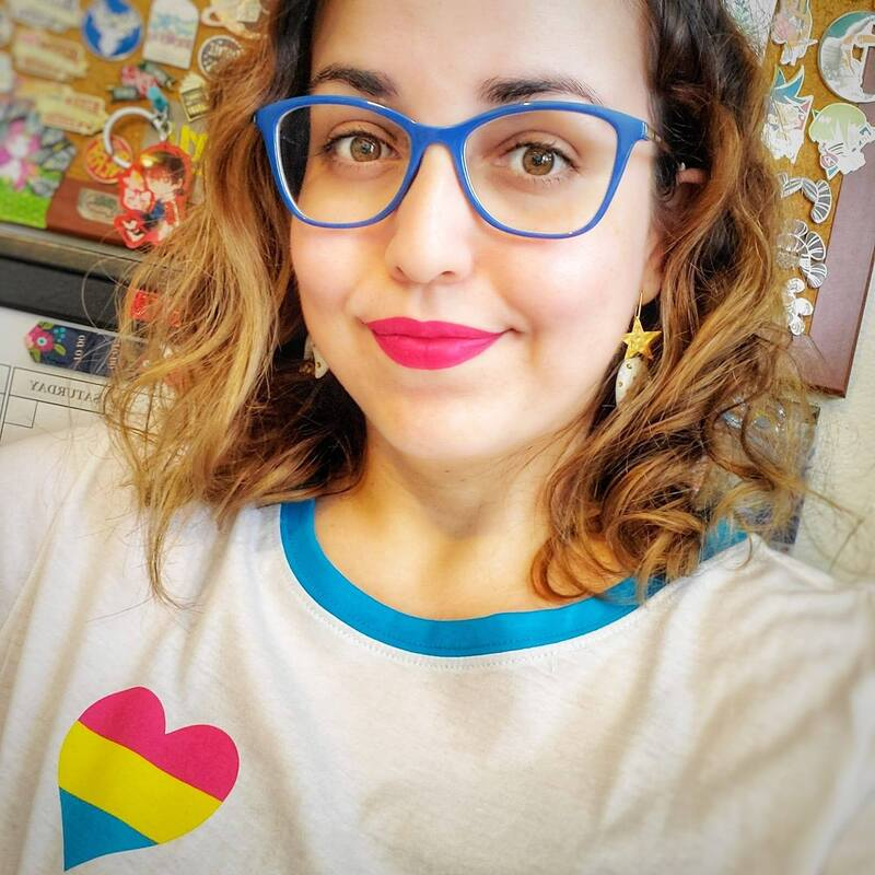 Amarilys 'Amy' Acosta. Shoulder-length light brown curls, butterfly-wing blue eyeglasses, white shirt with heart-shaped pansexual flag, and electric pink lips.